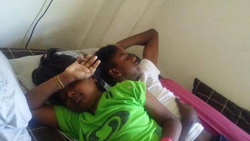 Kids in bed, eyes shut against the sunlight.